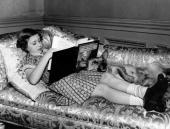Princess Margaret Rose younger daughter of King George VI and Queen Elizabeth reading on the sofa at Windsor Castle accompanied by Jane the corgi