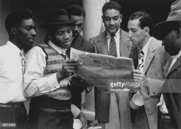 Jamaicans reading a newspaper whilst on board the extroopship 'Empire Windrush' bound for Tilbury docks in Essex