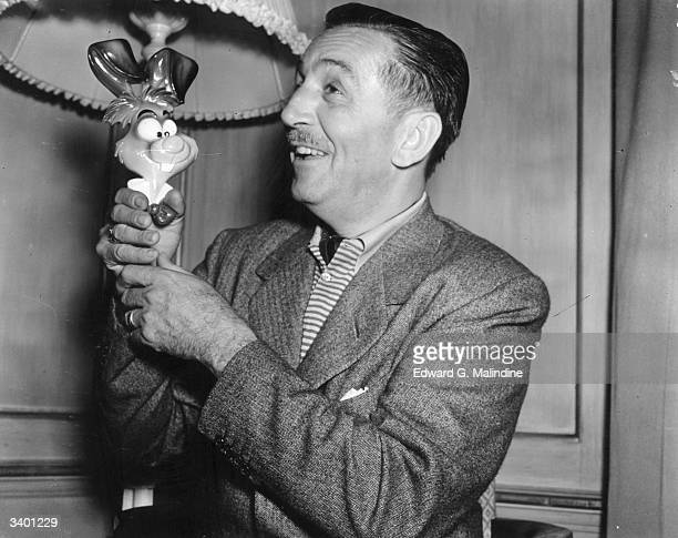 American animator and producer Walt Disney in London with one of the characters from his new film 'Alice In Wonderland'