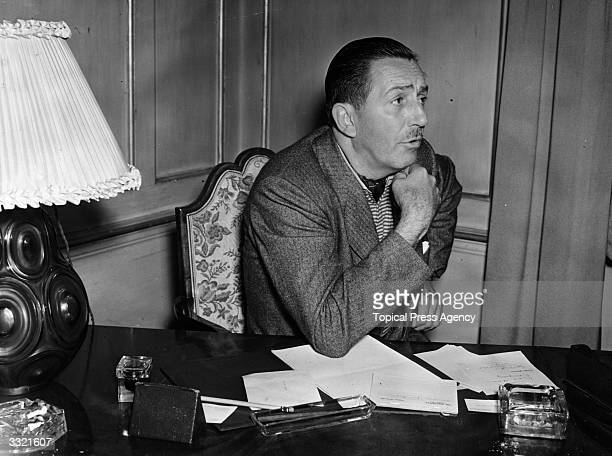 US artist and film producer Walt Disney creator of Mickey Mouse seated at a desk with paperwork in London
