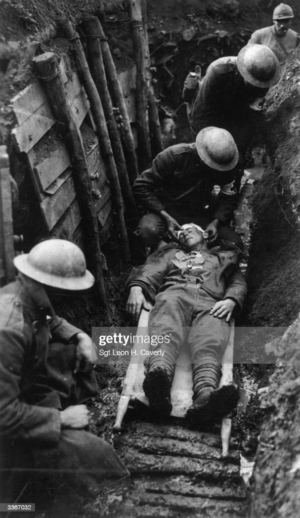 Red Cross workers in a trench tending to a wounded American soldier on a stretcher.