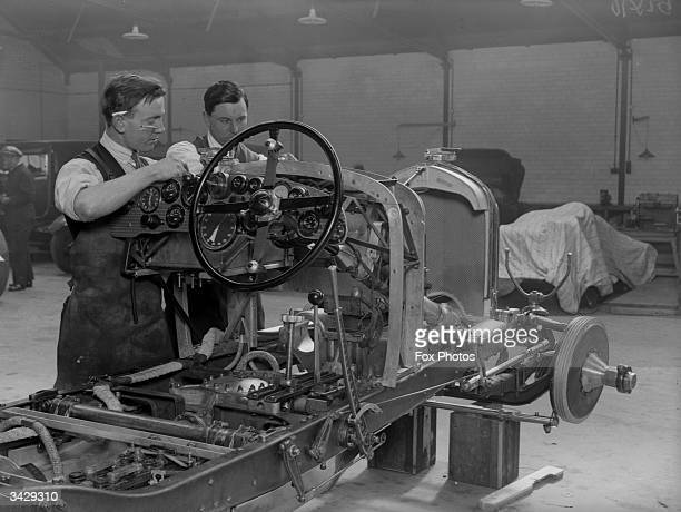 Mechanics at work on the body of a Bentley race car at a garage in Welwyn Hertfordshire