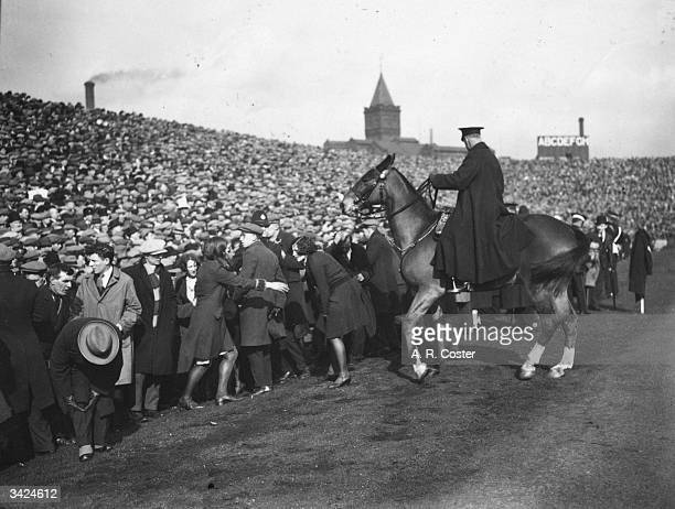 Mounted police push the crowd off the pitch during the FA Cup semifinal match between Sheffield Wednesday and Huddersfield at Manchester
