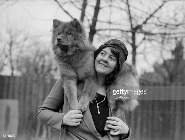 Mrs Bernard Cathbert drapes one of her chow dogs around her shoulders in the garden of Omar House Catford London