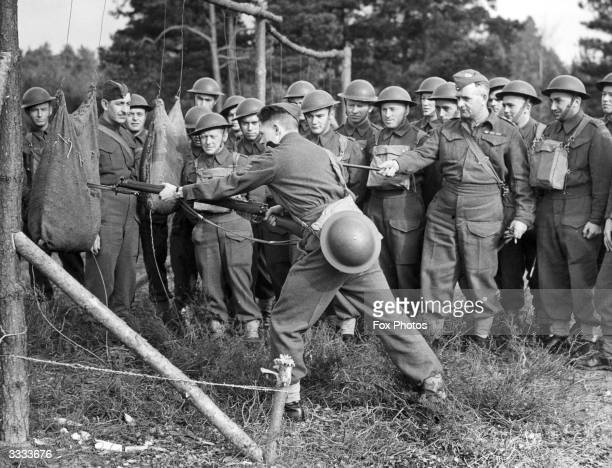 A Gaskatchewan regiment of Canadian soldiers is given instruction in bayonet fighting at a training camp Britain