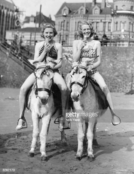 Two women enjoy ice cream as they ride donkeys on the sands at Blackpool