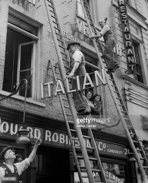Shopkeeper removing the word 'Italian' from the sign above his restaurant in Soho London during WW II after antiItalian riots throughout Britain
