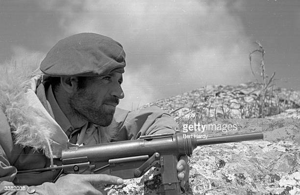 A Greek commando soldier wearing a furcollared jacket supplied by the Americans waits for a guerrilla target to emerge during the Greek Civil War...