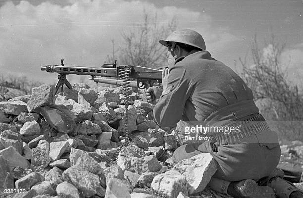 A Greek soldier keeps his machine gun at the ready on the lookout for guerrilla troops during the Greek Civil War Original Publication Picture Post...