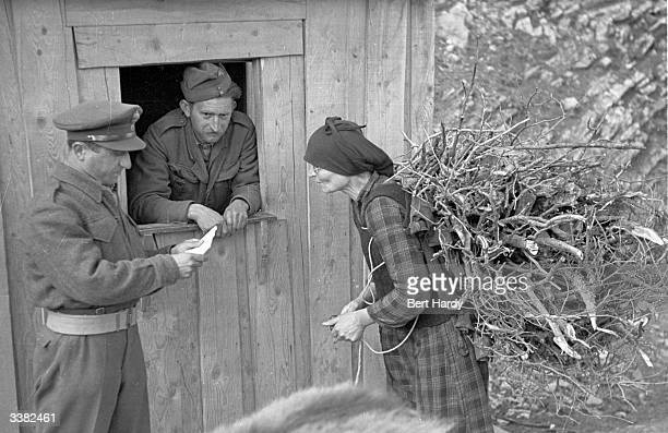 A Greek woman checks in with the village patrol for the evening curfew during the Greek Civil War Original Publication Picture Post 4551 The War For...