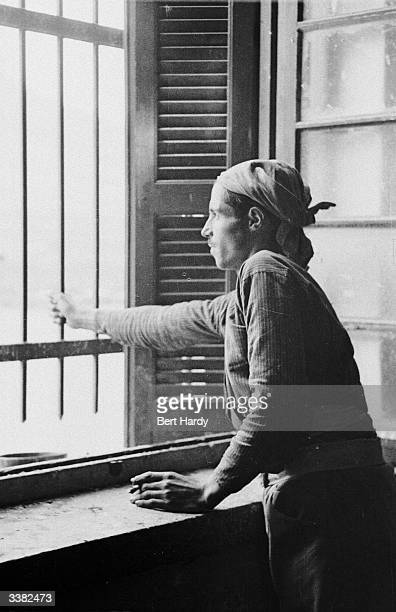 A man looks out through the bars on his window during the Greek Civil War Simply being in contact with a rebel soldier is grounds enough for...