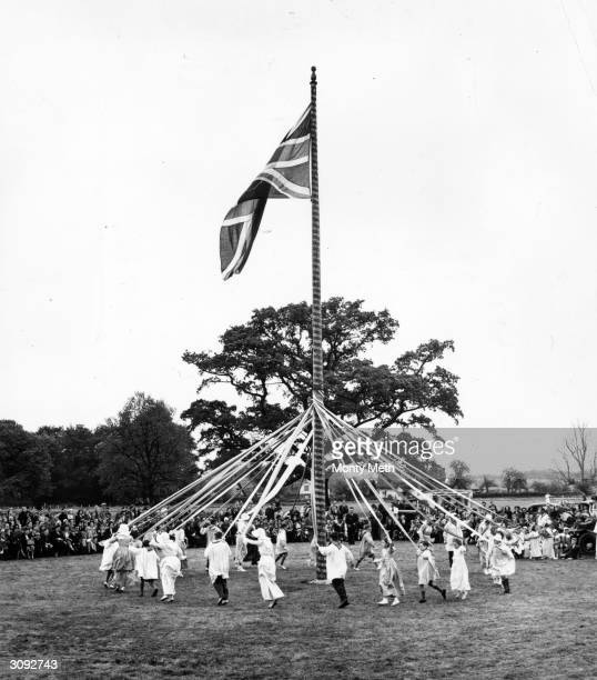A union jack flies over children dancing round a maypole on Ickwell Green Bedfordshire exactly as they did 400 years ago and wearing 200 year old...