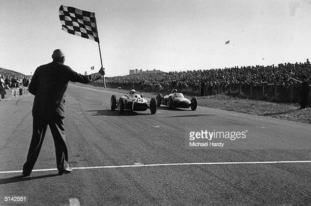 Stirling Moss driving a Lotus and Richie Ginther driving a Ferrari take the flag at Zandvoort in the Dutch Grand Prix