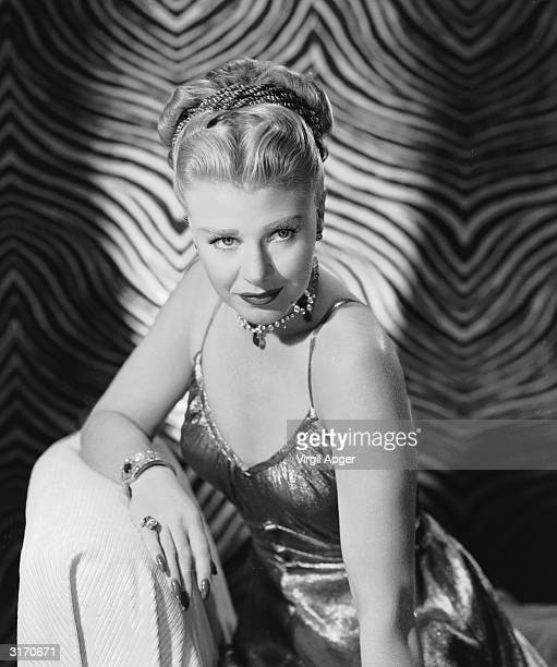 American actress Ginger Rogers wearing a metallic evening dress with shoulder straps and a jewelled choker for her role in 'The Barkleys Of Broadway'