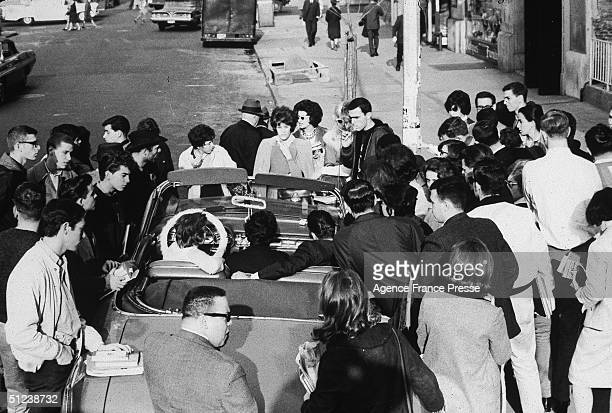 22nd November 1963 A crowd in New York gathers around a convertible car to listen to radio reports of President John F Kennedy's assassination