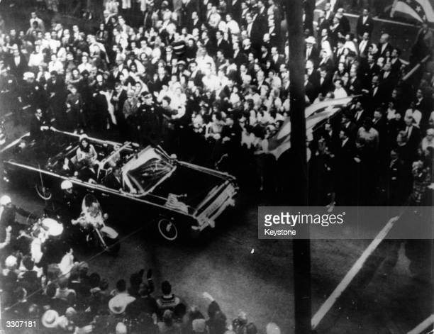 US statesman John F Kennedy 35th president of the US and his wife Jackie Kennedy travelling in the presidential motorcade at Dallas before his...