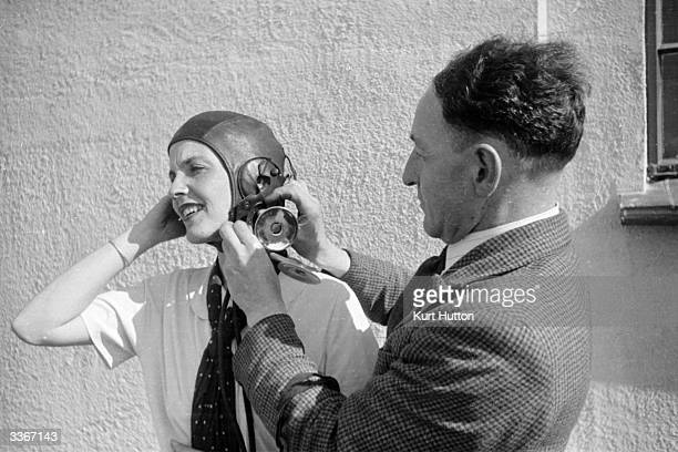 A male instructor assists in the donning of a flying helmet Women from all walks of life train one day a week to be pilots in the National Women's...