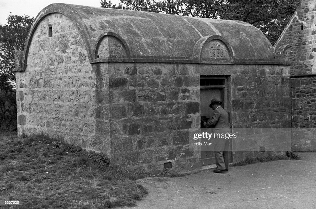 M Hamon, the Chief Constable of Sark examines the island's tiny police cell. Original Publication: Picture Post - 8 - She Rules An Island - pub. 1938
