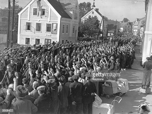 Ethnic Germans in the Sudetenland region of Czechoslovakia line the streets of Eger to greet soldiers on their return from Germany The men had fled...
