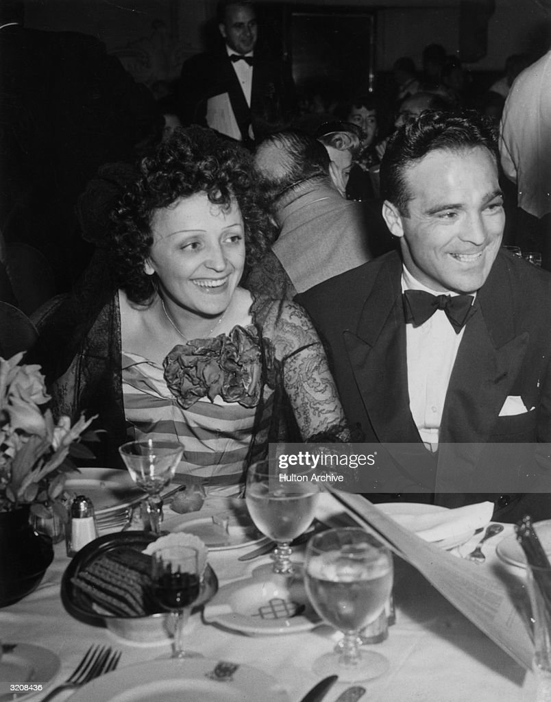 French singer Edith Piaf and French boxer <a gi-track='captionPersonalityLinkClicked' href=/galleries/search?phrase=Marcel+Cerdan&family=editorial&specificpeople=675823 ng-click='$event.stopPropagation()'>Marcel Cerdan</a> smile while sitting at a dining table at the Versailles nightclub, New York City.