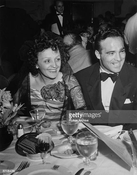 French singer Edith Piaf and French boxer Marcel Cerdan smile while sitting at a dining table at the Versailles nightclub New York City