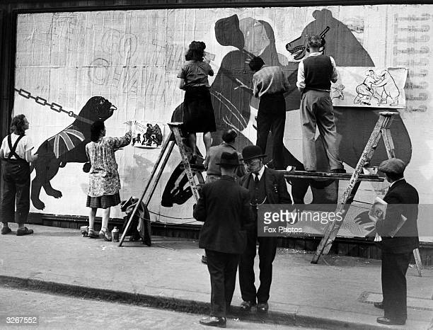 Working from a caricature women workers are among those in Fleet Street painting a large poster depicting Hitler at grips with the Russian bear...