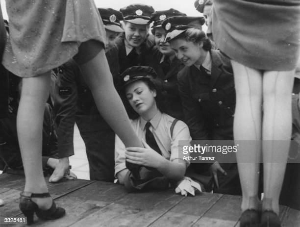 Servicewomen look at a design of artificial silkplated stocking called 731 specially designed for servicewomen at a fashion show at Kennards of...