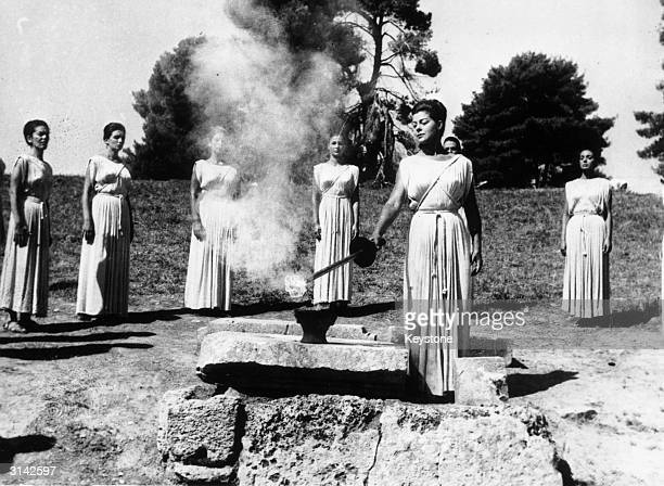 During the ancient ceremony at Olympia Greek actress Aleca Katseli lights the Olympic Torch which will be carried to Tokyo the site of the 1964...