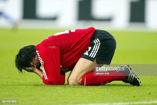 Sportler Fussball DStürmer kniet auf dem Rasen und schlägt sich die Hände vor das Gesicht