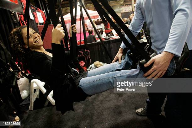 Denise Moore of Brampton has a chuckle while trying out the 'SwingSation' with her friend Ryan Pizale at right at Toronto's Automotive Building at...