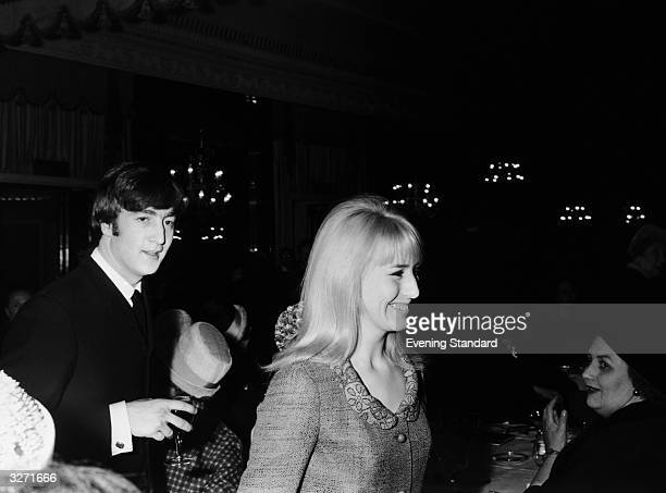 John Lennon singer songwriter and guitarist with British pop group the Beatles arrives at the Dorchester Hotel London with his wife Cynthia for a...