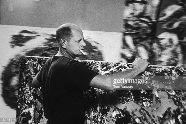 Abstract expressionist painter Jackson Pollock moves one of his paintings in his studio known as 'The Springs' in East Hampton New York