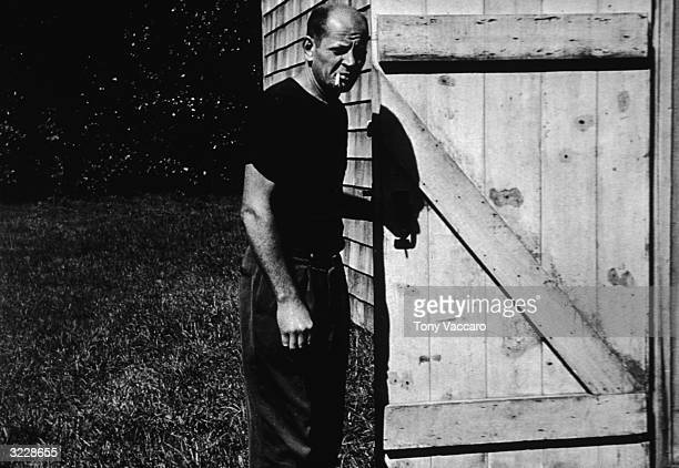 American painter Jackson Pollock smokes a cigarette while standing outdoors at the barn door of his studio 'The Springs' East Hampton New York