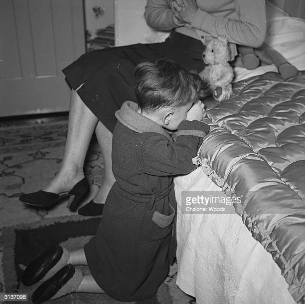 A mother sits on a bed to hear her young son in dressing gown and slippers kneel beside her to say his prayers
