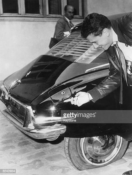 A man examines one of the bullet holes in French president General de Gaulle's Citroen DS in Paris after an assassination attempt in the Paris suburb...