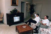 US President Ronald Reagan sits on a sofa with Vice President George Bush watching First Lady Nancy Reagan's national televised speech at the GOP...