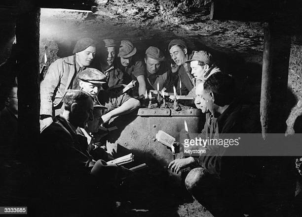 The Rev RN Timms and local Methodist minister the Rev G Hunt conduct a Christmas Carol Service 200 feet below ground for a group of coal miners at...