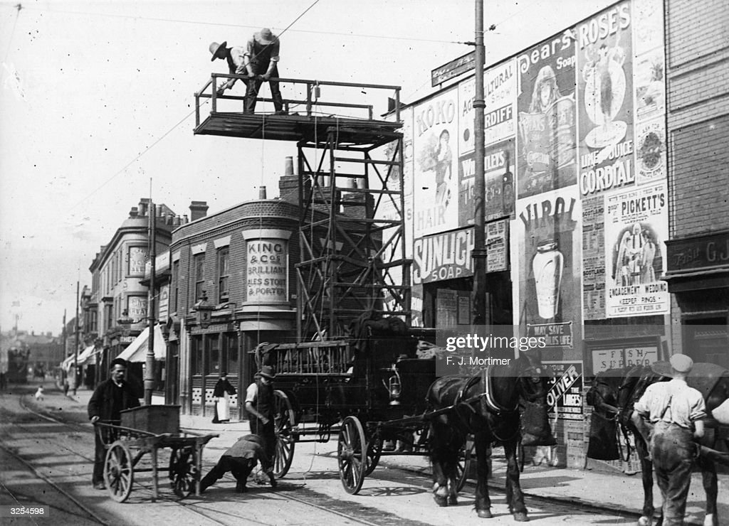 Workmen erecting the overhead wires in Commercial Road for the electric tram from a tower wagon in Portsmouth