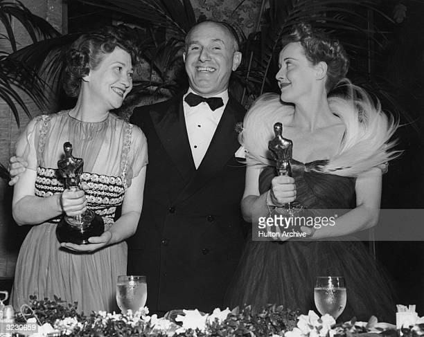 American film studio head Jack Warner poses with his arms around American actors Fay Bainter and Bette Davis who hold their Oscars for director...