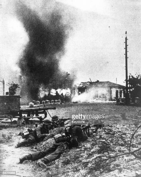 German soldiers dislodged from a house on the outskirts of Kharkov which has been set on fire taking cover outside the building