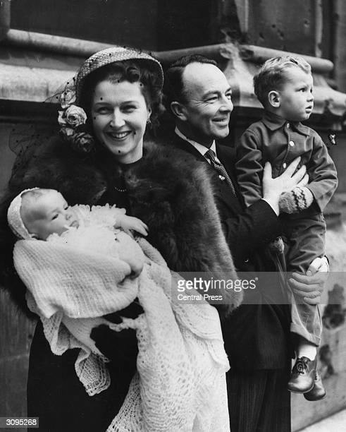 British politician and AttorneyGeneral Sir Hartley Shawcross and his wife Joan at the christening of their baby daughter Joanna in the crypt of the...