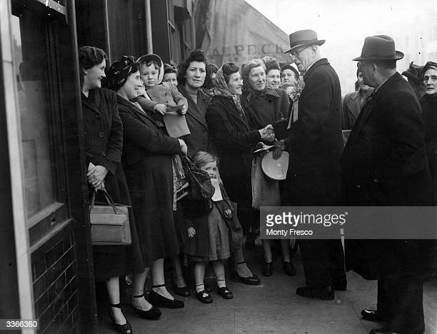 Liberal Party Parliamentary candidate Sir Percy Harris chats to women in a queue in Bethnal Green on the day of the general election