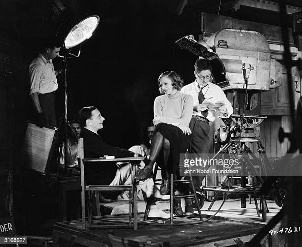 Swedish actress Greta Garbo talking with cast and crew members on the set of the film 'Anna Christie'