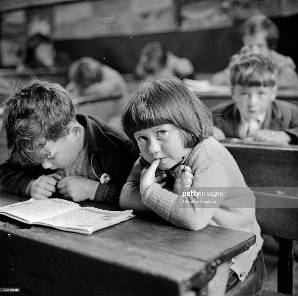 Two young schoolchildren sharing a textbook in a school on one of the Hebridean islands. These children have spoken Gaelic for most of their lives and are taught English at school as a foreign language. It is becoming increasingly important for the islanders to learn English as they have become less isolated from the rest of Scotland through an air service which has significantly shortened the journey time to the mainland. This generation is also more likely to leave the Western Isles to seek employment, and fluency in English will be essential. Original Publication: Picture Post - 7876 - The Last Of The Gaelic - pub. 1955