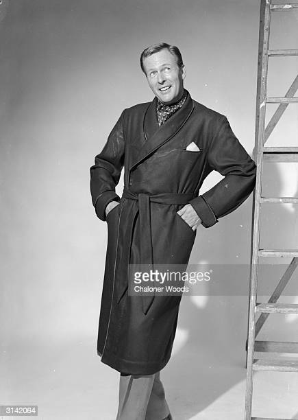 A happy looking man wearing a dressing gown and a cravat leaning against a ladder