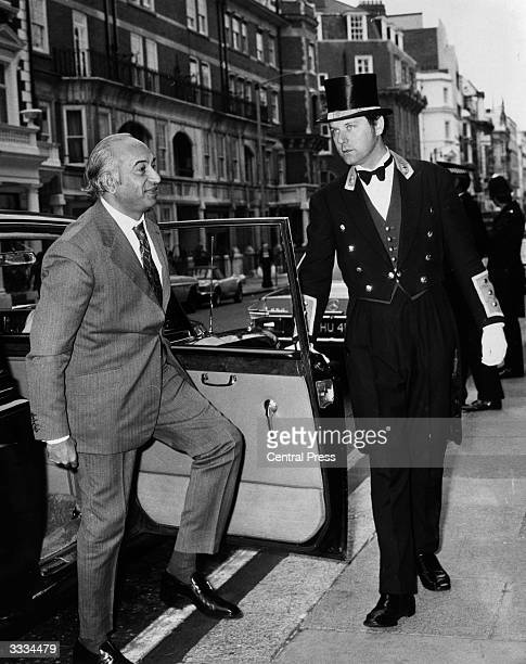 A doorman at Claridges Hotel holds a car door open for President Bhutto of Pakistan as he arrives at the hotel whilst on a visit to London