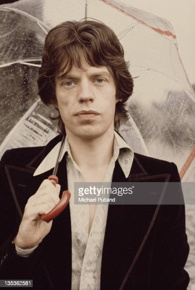 Singer Mick Jagger of the Rolling Stones posed holding an umbrella at Carmarthen Castle in Wales on 23rd July 1973