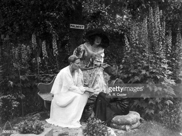 The British actress Nancy Price and a clairvoyant on the seat in the Blue Garden where Charles II used to sit with Nell Gwyn Behind them Mrs Patrick...