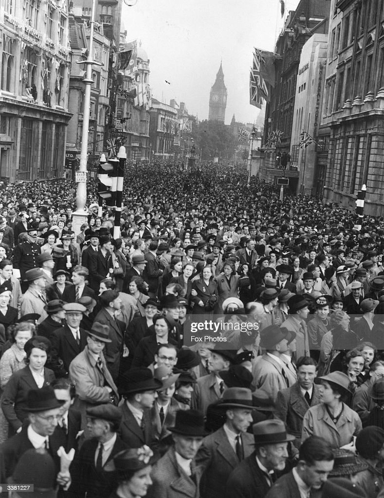 Crowds filling Whitehall to watch King George VI and Queen Elizabeth pass on their way to Buckingham Palace from Waterloo. Big Ben can be seen in the background.