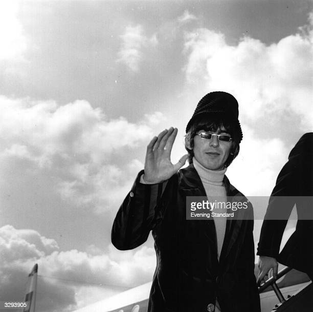 George Harrison of pop group The Beatles waves goodbye to fans and the press as he boards an aeroplane at London Airport